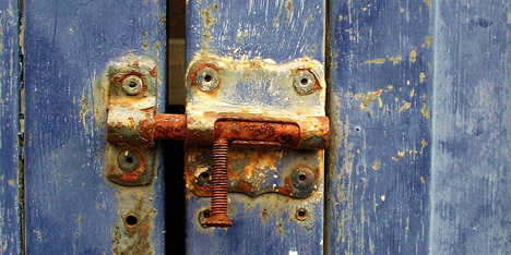A rusty lock on a wooden door